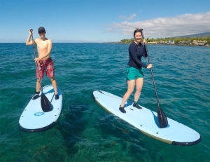 A couple of paddle boarders enjoying a beautiful day in Kona, Hawaii