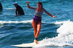 Woman surfer cross steping on a longboard while on a surf trip